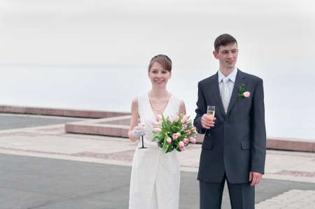 Young loving wedding couple with bunch of flowers. Newlywed pair Stock Photo - 7135168