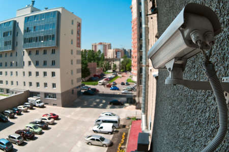 private security: Optical camera on wall of building watching on parking place from top Stock Photo