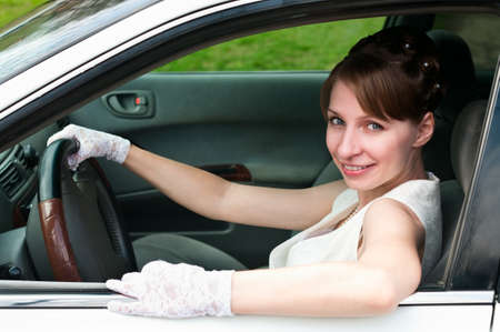 Woman in white dress and white-gloved sitting in car as a driver. Looking at camera photo