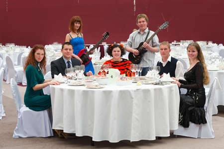 Five young people at round white table in restaurant and two artists with guitars. Dinner party photo