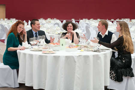 Five young people at round white table in restaurant. Dinner party photo