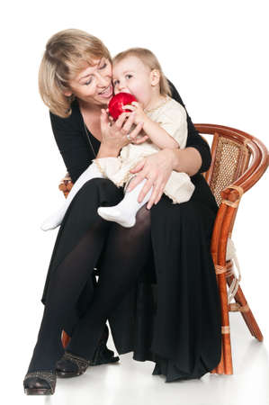 Middle age woman eating red apple with little child a granddaughter. Isolated on white background photo