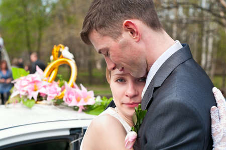 Young loving wedding couple with bunch of flowers. Newlywed pair photo