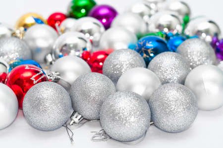 Four grey Christmas balls on foreground and many color balls on background photo
