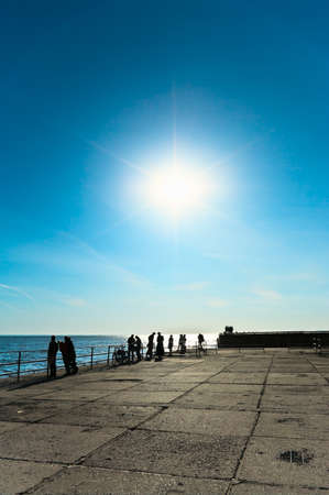 Bright sun on blue sky. Sea coast with people photo