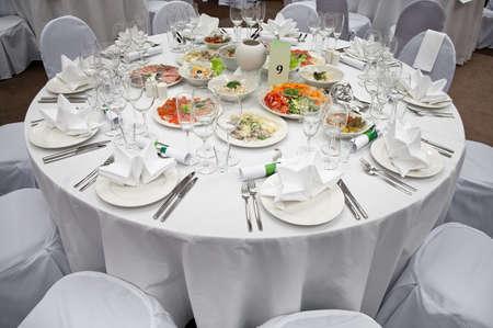 mesa para banquetes: Lugar de recepci�n de boda blanca listo para hu�spedes. Tablas de elegante banquete preparadas para una Conferencia o un partido.