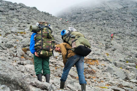 knapsacks: Two tired backpackers in mountains with knapsacks Stock Photo