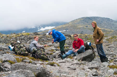 Group of travelers in mountains with knapsacks are resting photo