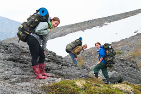 knapsacks: Tired team of backpackers in mountains with knapsacks