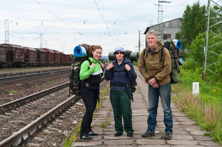 Group of travelers on railway station waiting a train. Mountaineering with knapsacks photo