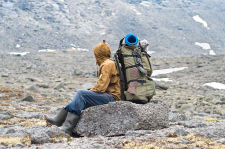 Backpacker a senior man sitting on rock in mountains Stock Photo - 7927348