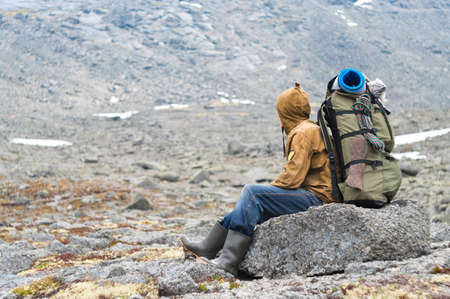 Backpacker a senior man sitting on rock in mountains Stock Photo - 7927349