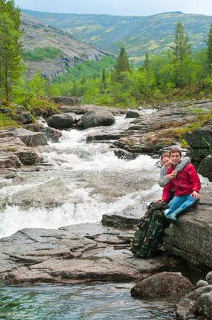 Woman embracing young man near waterfall in mountains photo