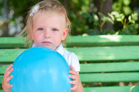 Little girl with blue air balloon sitting o bench photo