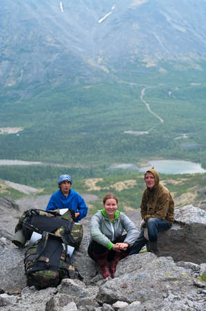 knapsacks: Group of travelers in mountains with knapsacks are resting