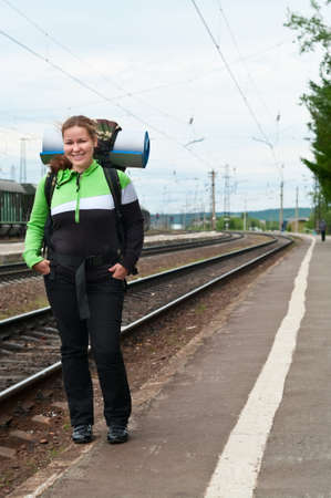 Backpacker a young woman waiting train on railway station photo