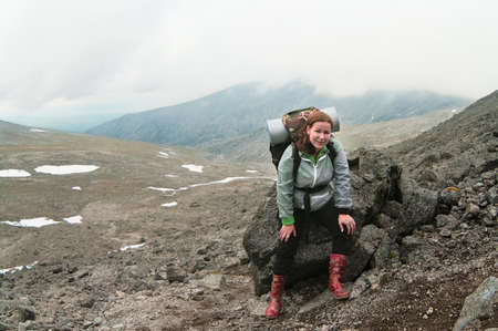 Backpacker a young woman sitting on rock in mountains photo