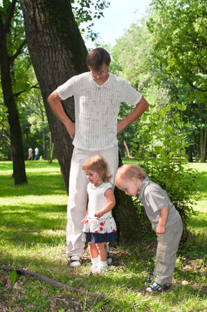 Father and little children in park in summer day playing photo