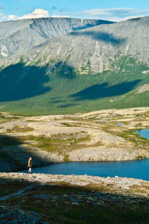 Man in mountain standing near lake and looking at camera from far away Stock Photo - 7935625