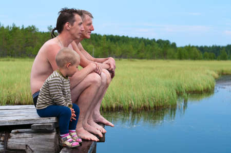 Father, son and grandson on wooden pier near a lake in swimming trunks photo