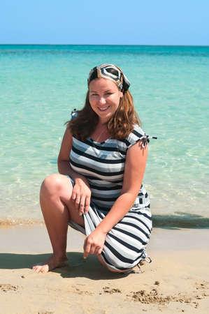 Young pretty girl on a sandy beach near the shore blue sea Stock Photo - 8267092