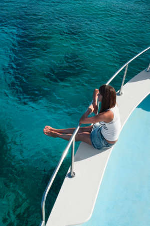 Young beautiful girl sitting on a yacht with his legs hanging in the blue sea photo