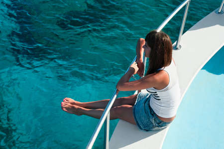 Young beautiful girl sitting on a yacht with his legs hanging in the blue sea Stock Photo - 8267089