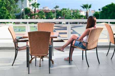 Hermosa joven sentado en una silla en el balcón del hotel y se ve en la distancia. Una mujer de raza blanca es parte trasera