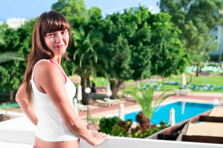 Young beautiful girl standing on the balcony of the hotel and looking at camera. One Caucasian woman smiling close up Stock Photo - 8780290