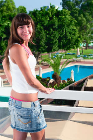 Young beautiful girl standing on the balcony of the hotel and looking at camera. One Caucasian woman smiling close up Stock Photo - 8780289