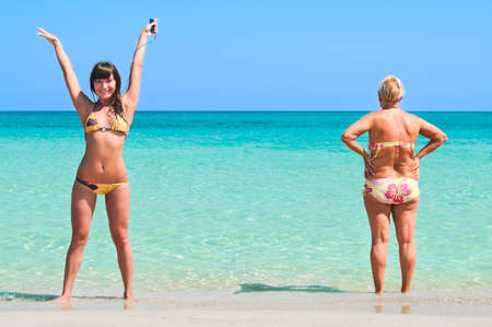aging woman: Young sexy girl and senior women standing on sandy beach near the sea.