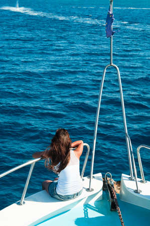 Women on yacht in blue sea seating on stern. photo