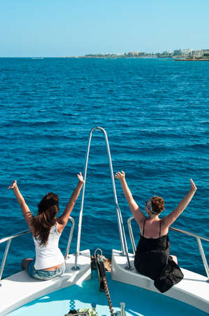 Two women on yacht seating on stern in blue sea photo