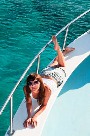 Young beautiful girl laying on a yacht with his legs hanging in the blue sea photo