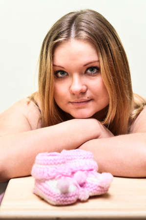 Pregnant young Caucasian woman looking at baby`s pink bootee.