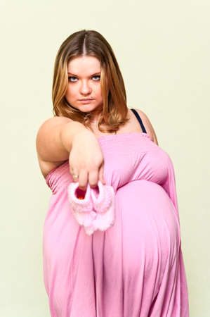 Pregnant young Caucasian woman holding in hands baby`s pink bootee. Stock Photo