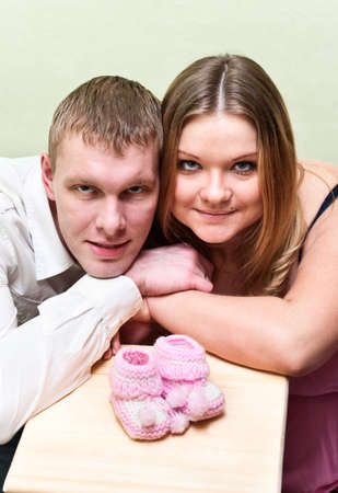 Pregnant woman with her husband looking at baby`s bootee. Caucasians, a loving young couple