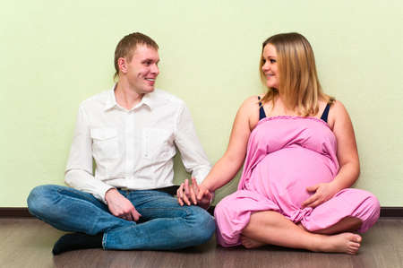 Pregnant woman with her husband sitting on floor in empty room. Caucasians, a loving young couple photo