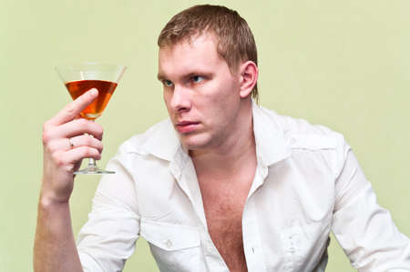 Handsome man sitting with glass of alcohol. Caucasian gay photo