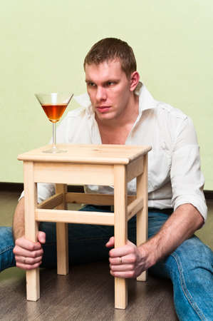 Drunken man sitting on floor with glass of alcohol and holding stool photo