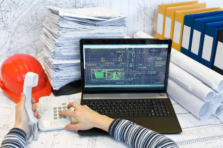 architect office: Male hands printing on loaptop and holding handset of phone. Documents are around. Stock Photo