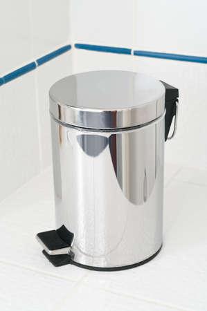 Refuse bin in room corner on white tile floor photo