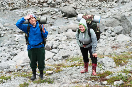 Two tired backpackers a young and mature women standing on rock in mountains photo