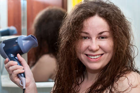 bushy: Young caucasian woman with curly brown bushy hair holding hairdryer