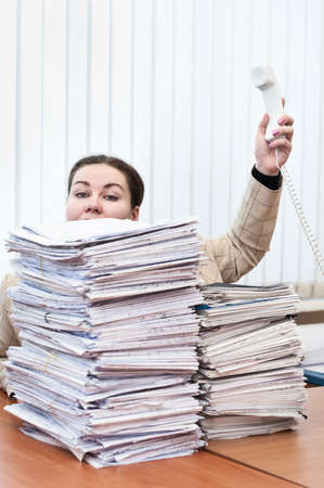 Telephone handset in hand of young caucasian woman behind pile from paper documents photo