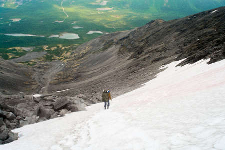 Man with backpack standing on snow in mountains Stock Photo - 9023436