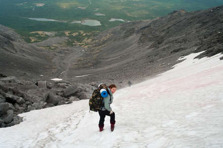 Backpacker a young woman standing on snow in mountains photo