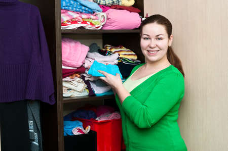 Young caucasian woman in the wardrobe packs things on a shelfs. photo