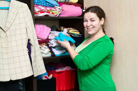 arrange: Young caucasian woman in the wardrobe packs things on a shelfs.