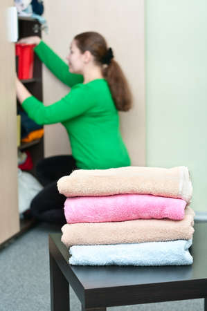 Stack of clothes and young caucasian woman arranging things in the wardrobe on background. photo